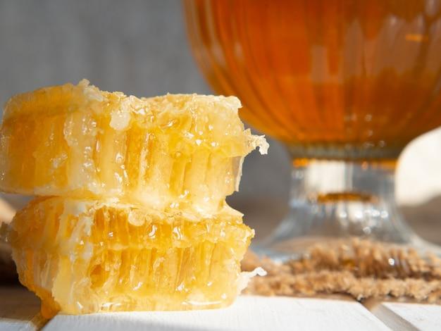 古い木製のテーブルに蜂蜜のクローズアップと蜂のハニカム