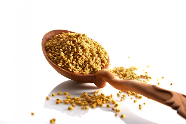 Bee pollen granules in a wooden spoon on a white background