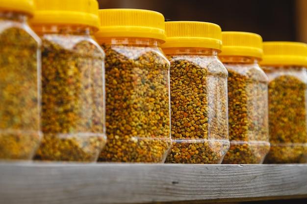 Bee pollen in a jar on a wooden shelf.
