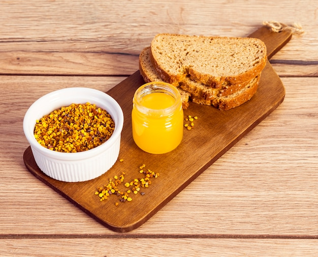 Bee pollen with honey and bread on wooden cutting board over desk