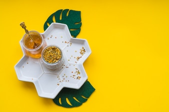 Bee pollens and honey in white tray on yellow background