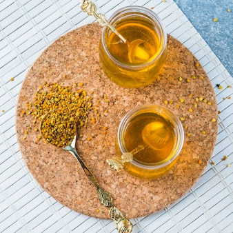 Bee pollens in spoon with honey pots on cork coasters