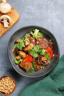 소나무 견과류 평면도와 쇠고기와 샴 피뇽. 콘크리트 테이블에 쇠고기와 버섯 샐러드.