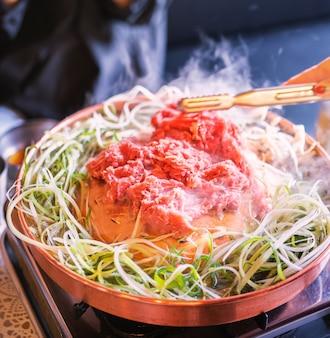 서울의 한국 식당에서 쇠고기 바베큐 불고기, 슬라이스 그릴이 달린 구리 냄비에 라이프 스타일의 신선한 한국 음식 요리, 가까이