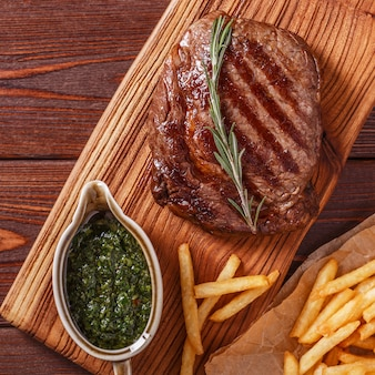 Beef barbecue ribeye steak with chimichurri sauce and french fries