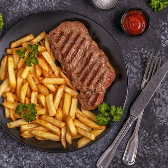 Beef barbecue steak with french fries, top view.