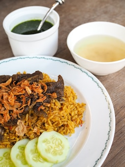Beef biryani with green chutney, yellow rice with beef