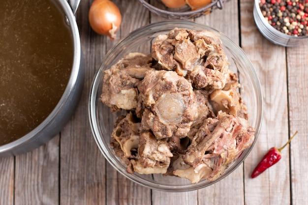 건강한 식단을 위해 수제 뼈 국물을 만드는 쇠고기 뼈. 테이블에 뼈 국물과 함께 냄비. 평면도