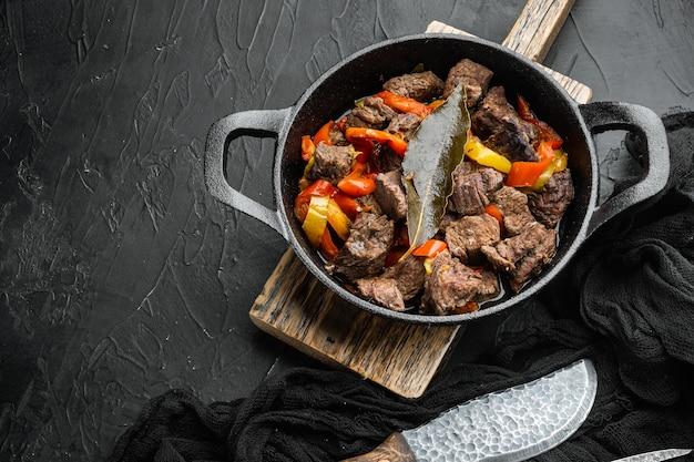 Тушеная говядина по-бургиньонски с овощами, на чугунной сковороде, на черном каменном фоне, с местом для текста