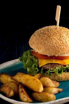 牛肉のハンバーガーとフライドポテトの黒い背景に。