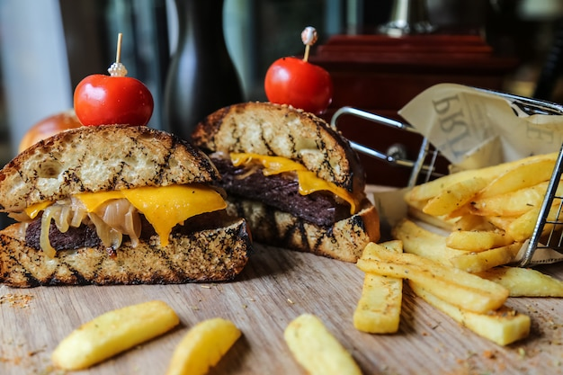 Beef burger cut in two pieces with french fries