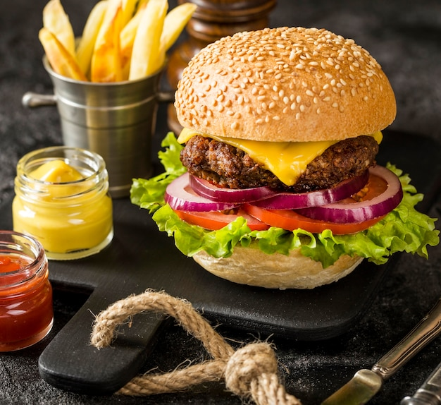 Beef burger on cutting board with fries and sauce