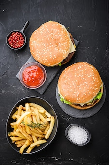 Beef burger and french fries on black, top view