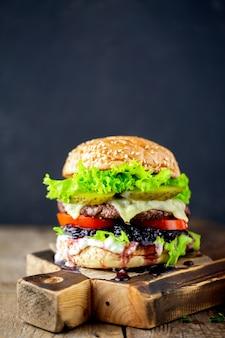 쇠고기 햄버거 검은 배경에 신선한 맛있는 햄버거 치즈와 함께 맛있는 구운 된 앵거스 햄버거.