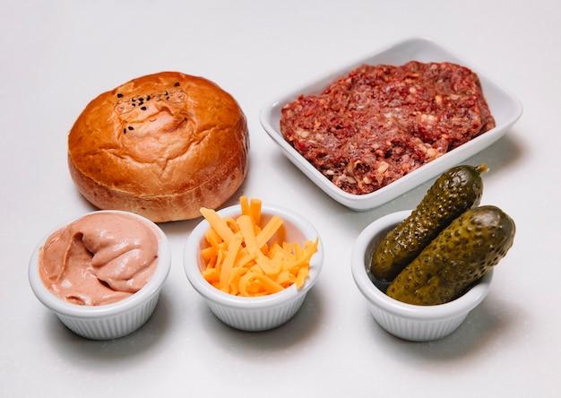 Ингредиенты для говяжьего бургера с фаршем из сырого фарша, огурцами, чеддером и соусом