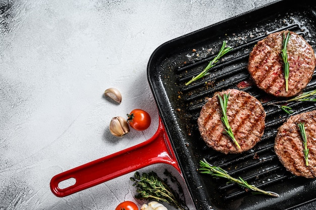 Beef burger patties sizzling on a hot barbecue pan. top view. copy space