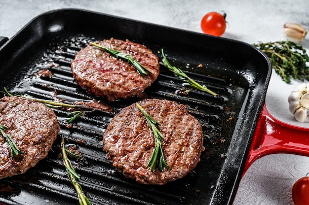Beef burger patties sizzling on a hot barbecue pan. top view