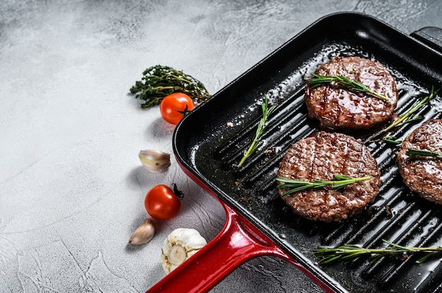 Beef burger patties sizzling on a hot barbecue pan