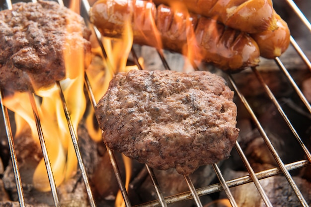Beef burger and sausages cooking over flames on grill