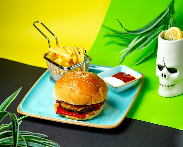 Beef burger served with french fires ketchup and mayonnaise
