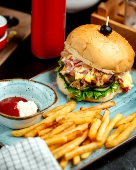 Beef burger served with french fries ketchup and mayonnaise