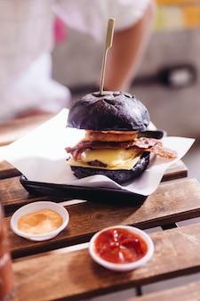 チーズ付きの黒パン付きのビーフバーガー