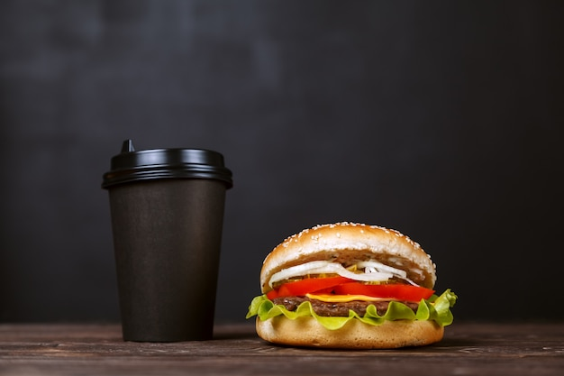 Beef burger with bacon and coffee in a black paper cup on a wooden table. cafe menu design concept