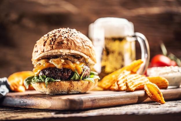 キャラメリゼした玉ねぎ、ルッコラ、溶けたチーズを背景にポテトウェッジと生ビールを添えたビーフバーガー。
