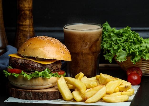 Бургер из говядины с сыром, листьями салата, помидорами, подается с картофелем фри и колой