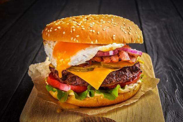 Бургер из говядины с плавленым сыром и беконом и яйцом на деревянных фоне.