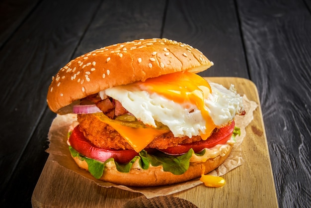 Beef burger with melted cheese and bacon and egg on wooden background.