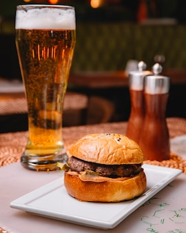 Beef burger with sauce pickled cucumber served at restaurant with beer vertical