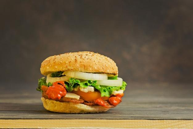 ソーセージ、玉ねぎのマリネ、トマト、レタス、ソース、木の板と牛肉のハンバーガー。暗い素朴な木製の背景に牛肉のアメリカのハンバーガー。ファーストフードやストリートフードのコンセプト