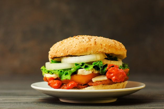 Beef burger with sausage, marinated onion, tomatoes, lettuce, sauce and on a wooden  board.