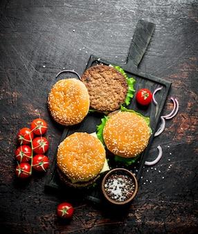 어두운 시골 풍 테이블에 커팅 보드에 그릇에 쇠고기 햄버거와 향신료