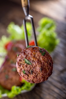 Котлеты фрикадельки из говяжьих гамбургеров с салатом из салата, томатом, луком на деревянной доске.