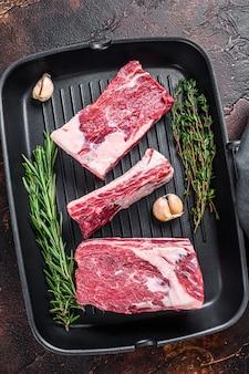 그릴 팬에 쇠고기 송아지 갈비 고기 요리 준비. 어두운 배경. 평면도.