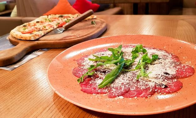 ビーフカルパッチョ、ビーフテンダーロイン、ズッキーニ、ケーパー、ペパロニピザをイタリアンレストランのテーブルでお召し上がりいただけます。