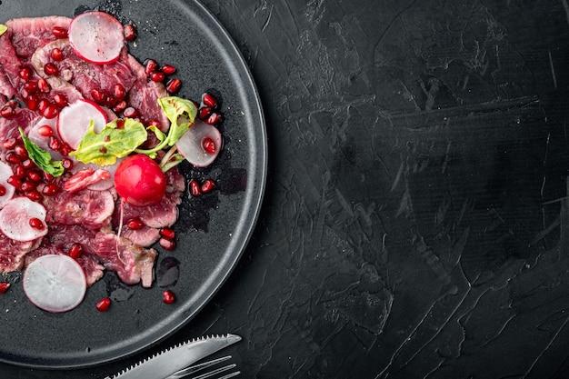 ビーフカルパッチョ冷製前菜セット、大根とガーネット、プレート、黒い石の背景、上面図フラットレイ、テキスト用のコピースペース