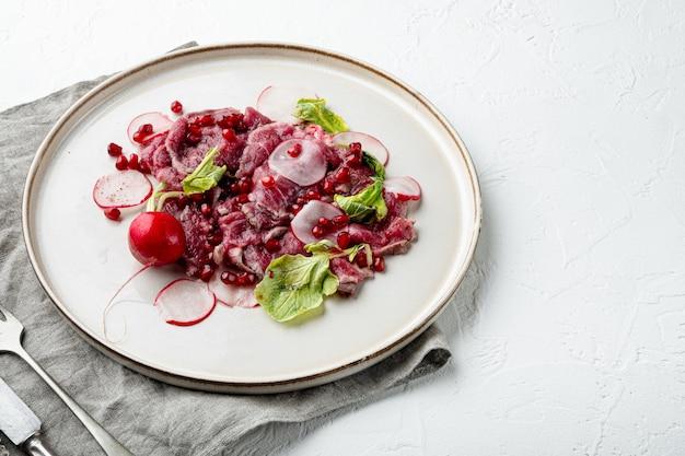 牛肉のカルパッチョ冷製前菜セット、大根とガーネット、プレート、白い石の背景、テキストのコピースペース
