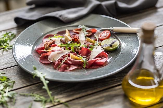 乾燥トマトのアーティチョークルッコラとパルメザンチーズを添えたプレート上の牛肉のカルパッチョ。