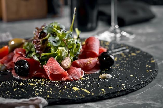 Карпаччо из говядины с рукколой на черной тарелке, традиционная итальянская кухня. темный ключ, скопируйте пробел. вид сверху