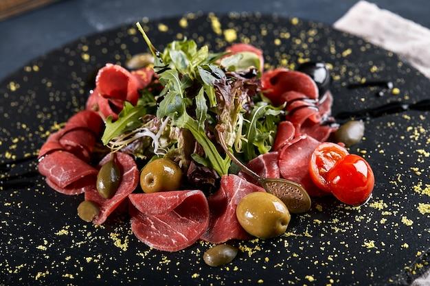 黒いプレートにルッコラを添えた牛肉のカルパッチョ、伝統的なイタリア料理。ダークキー、コピースペース、