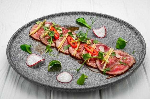 ダークプレートににんにく、醤油、唐辛子、オリーブオイルを添えた牛肉のカルパッチョ