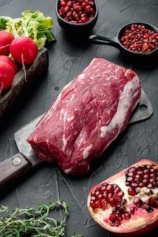 Карпаччо из говядины с редисом, сыром пармезан и ингредиентами из рукколы на черном каменном фоне