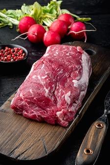 Карпаччо из говядины с редисом, пармезаном и ингредиентами из рукколы на черном фоне деревянного стола