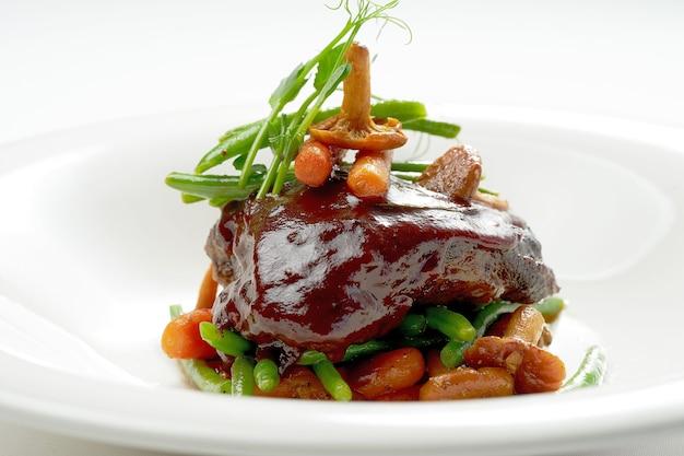 Стейк из говяжьей щеки, карамелизированный в винном соусе с лисичками и спаржей в белой тарелке. изолированные на серой поверхности.