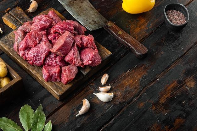 Набор ингредиентов для тушеного мяса из говяжьей вырезки на старом темном деревянном столе с местом для текста