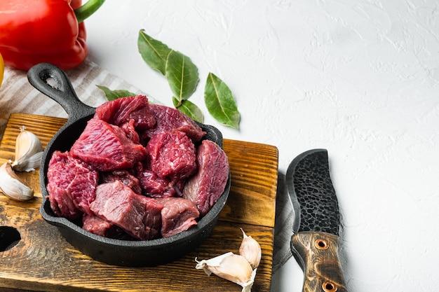 Ингредиенты для тушеного мяса из говяжьего чака со сладким болгарским перцем в чугунной сковороде на белой каменной поверхности с местом для текста