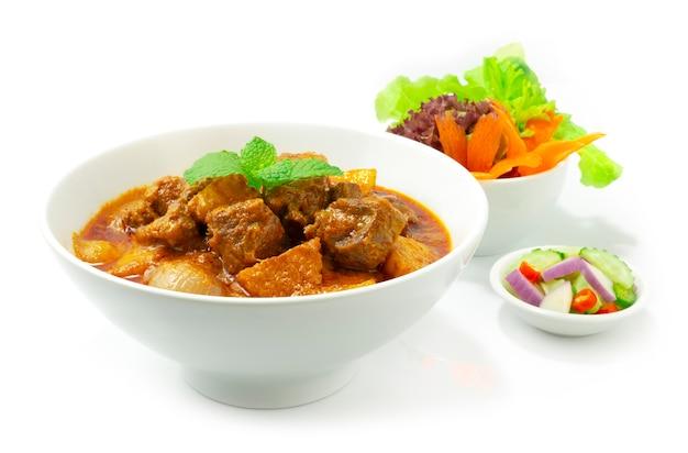 ビーフカレーマッサマンアジア料理スタイルのarjad(キュウリ、オニオ、酢の唐辛子)が野菜のサイドビューを飾る